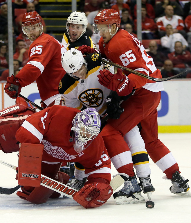 . Boston Bruins center Noel Acciari (55) is defended in front of the net by Detroit Red Wings defenseman Danny DeKeyser (65) as Red Wings goalie Jimmy Howard (35) manages to clear the puck during the third period of an NHL hockey game Saturday, Oct. 29, 2016, in Detroit. (AP Photo/Duane Burleson)
