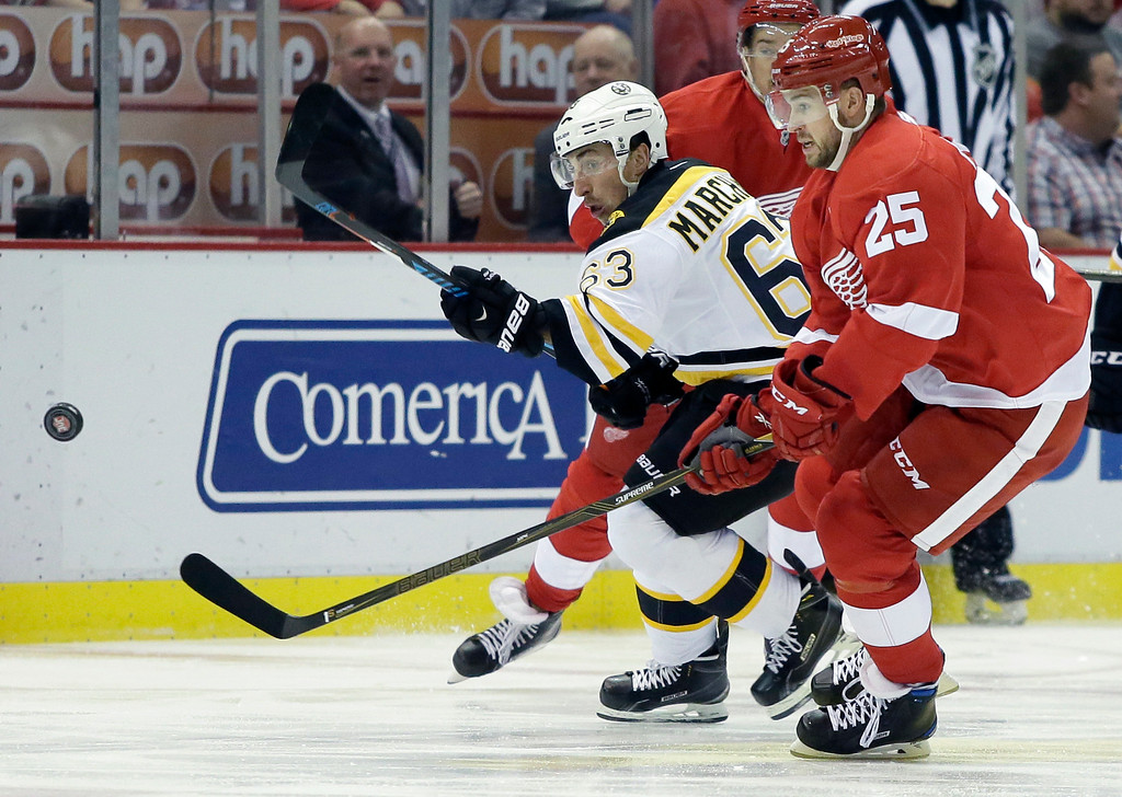 . Boston Bruins left wing Brad Marchand (63) races Detroit Red Wings defenseman Mike Green (25) to the puck during the first period of an NHL hockey game Saturday, Oct. 29, 2016, in Detroit. (AP Photo/Duane Burleson)