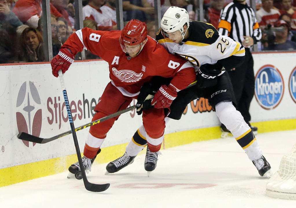 . Detroit Red Wings left wing Justin Abdelkader (8) tries to maintain control of the puck against Boston Bruins defenseman Brandon Carlo (25) during the second period of an NHL hockey game Saturday, Oct. 29, 2016, in Detroit. (AP Photo/Duane Burleson)