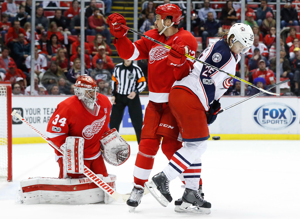 . Columbus Blue Jackets center William Karlsson (25) is hit by a shot on Detroit Red Wings goalie Petr Mrazek (34) as defenseman Jonathan Ericsson (52) defends in the third period of an NHL hockey game Tuesday, Feb. 7, 2017, in Detroit. (AP Photo/Paul Sancya)