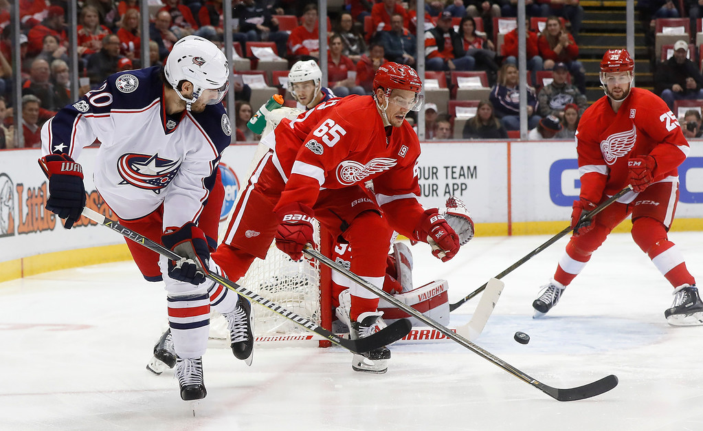 . Columbus Blue Jackets left wing Brandon Saad (20) flips the puck towards the net as Detroit Red Wings defenseman Danny DeKeyser (65) defends in the first period of an NHL hockey game Tuesday, Feb. 7, 2017, in Detroit. (AP Photo/Paul Sancya)