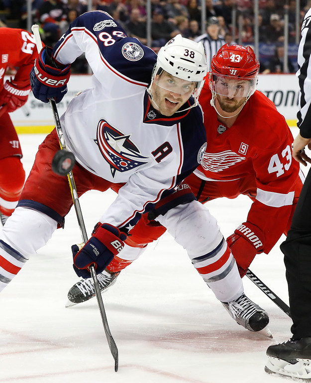 . Columbus Blue Jackets center Boone Jenner (38) and Detroit Red Wings center Darren Helm (43) watch the puck during a face-off in the second period of an NHL hockey game Tuesday, Feb. 7, 2017, in Detroit. (AP Photo/Paul Sancya)