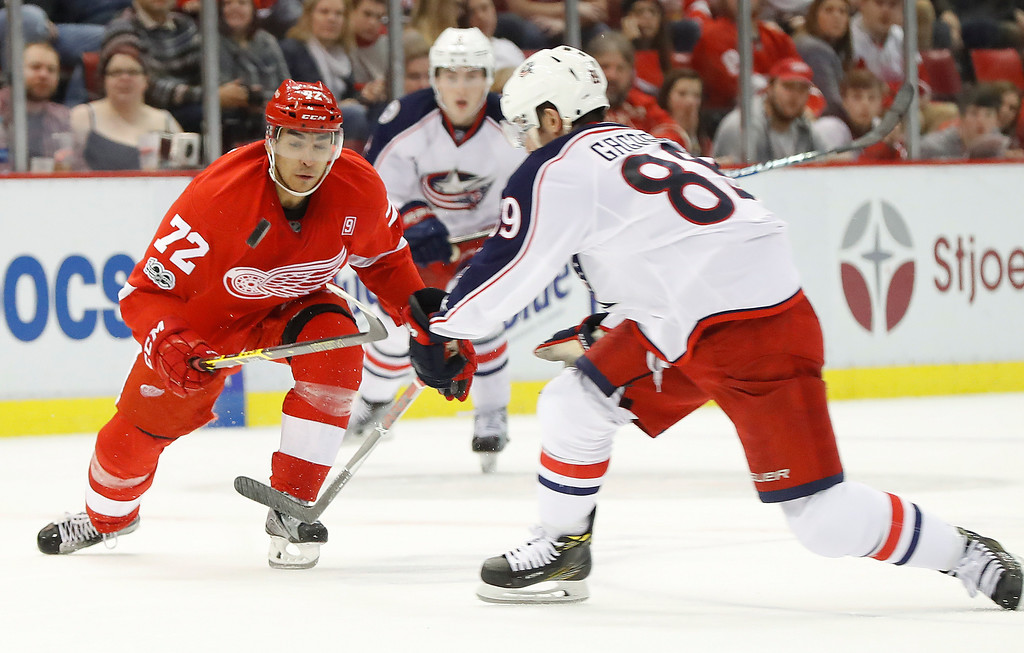 . Detroit Red Wings center Andreas Athanasiou (72) and Columbus Blue Jackets center Sam Gagner (89) battle for the puck in the second period of an NHL hockey game Tuesday, Feb. 7, 2017, in Detroit. (AP Photo/Paul Sancya)