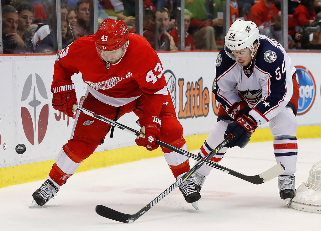. Detroit Red Wings center Darren Helm (43) and Columbus Blue Jackets defenseman Scott Harrington (54) battle for the puck in the second period of an NHL hockey game Tuesday, Feb. 7, 2017, in Detroit. (AP Photo/Paul Sancya)