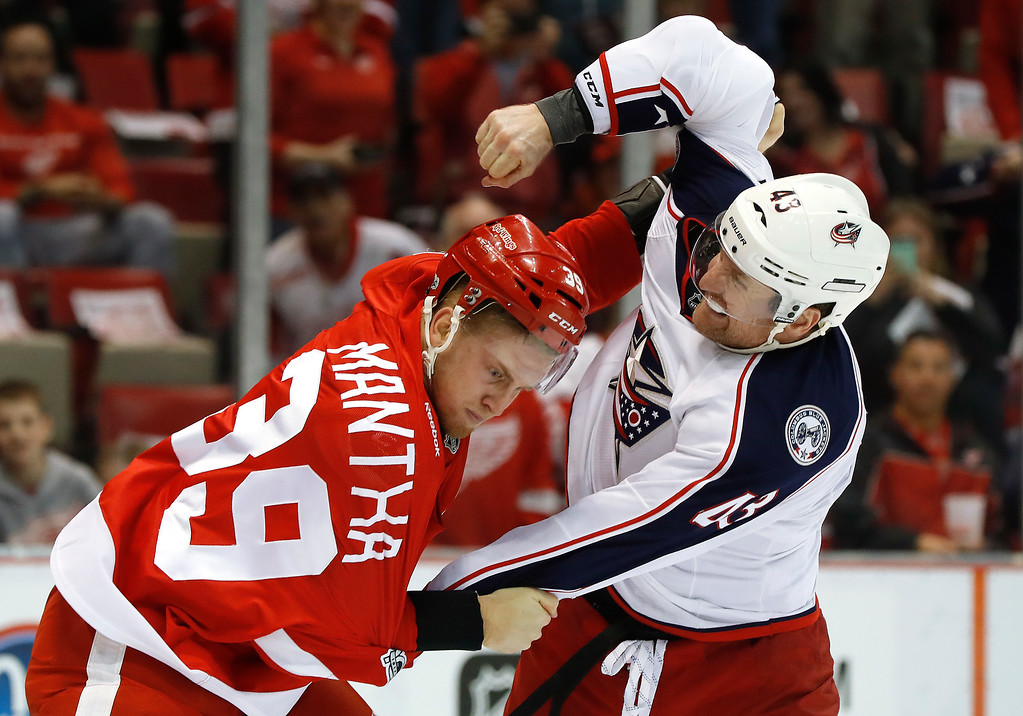 . Detroit Red Wings right wing Anthony Mantha (39) fights with Columbus Blue Jackets left wing Scott Hartnell (43) in the first period of an NHL hockey game Tuesday, Feb. 7, 2017, in Detroit. (AP Photo/Paul Sancya)