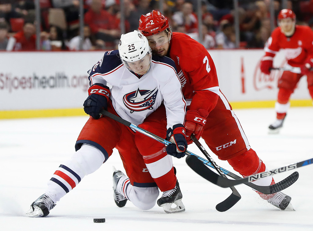 . Columbus Blue Jackets center William Karlsson (25) and Detroit Red Wings defenseman Brendan Smith (2) battle for the puck in the second period of an NHL hockey game Tuesday, Feb. 7, 2017, in Detroit. (AP Photo/Paul Sancya)