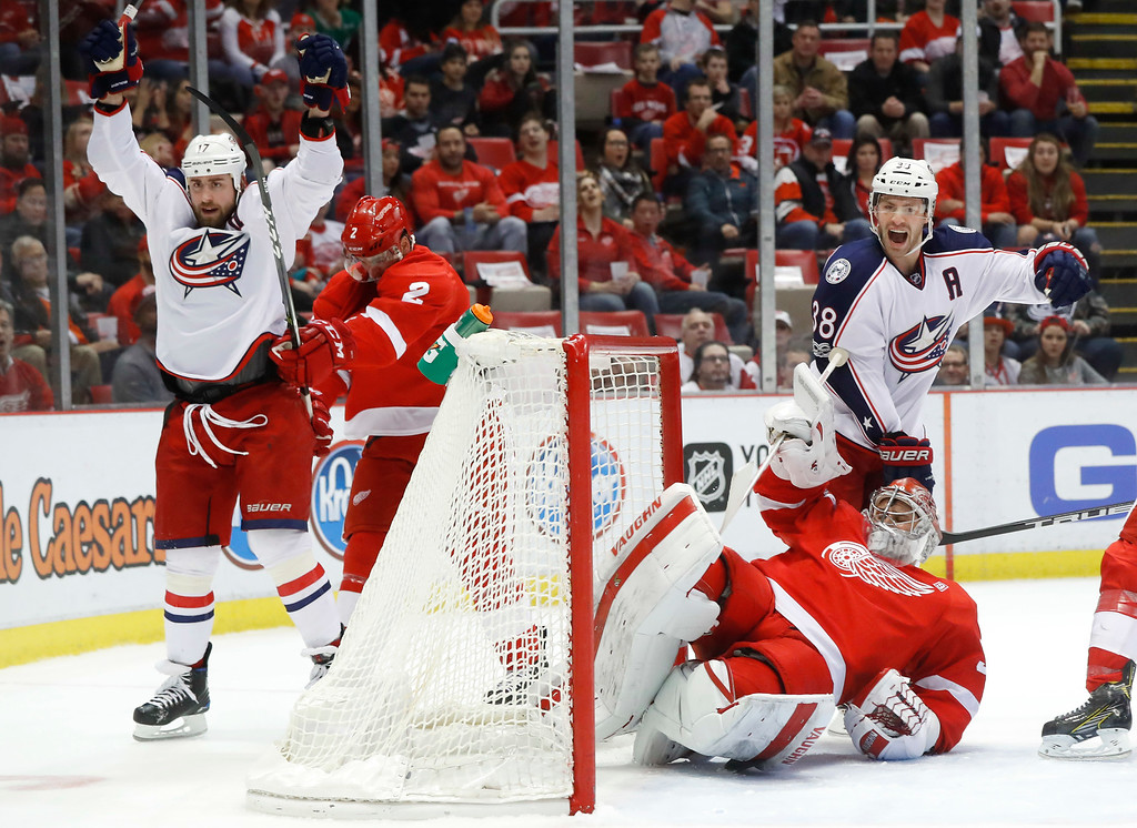 . Columbus Blue Jackets center Brandon Dubinsky, left, celebrates his goal against Detroit Red Wings goalie Petr Mrazek (34) as Boone Jenner (38) looks on in the first period of an NHL hockey game Tuesday, Feb. 7, 2017, in Detroit. (AP Photo/Paul Sancya)