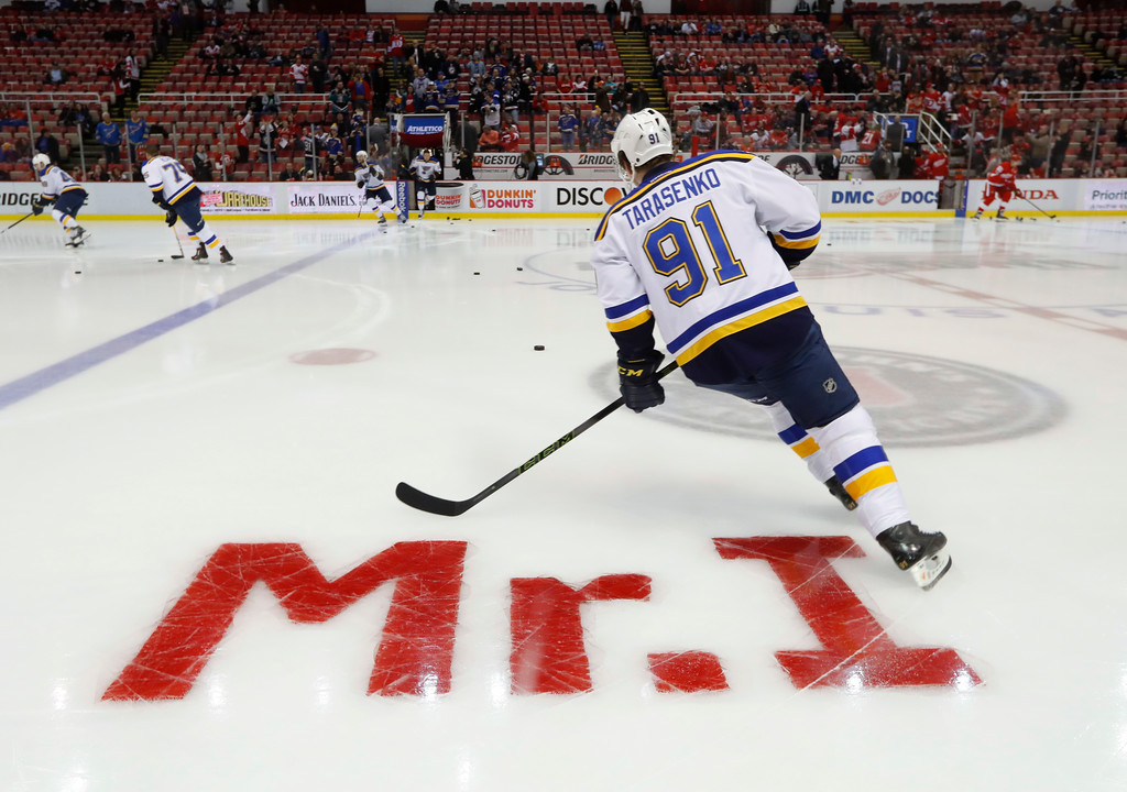 . St. Louis Blues\' Vladimir Tarasenko skates past a tribute to Mike Ilitch painted on the ice at Joe Louis Arena before an NHL hockey game against the Detroit Red Wings, Wednesday, Feb. 15, 2017, in Detroit. Billionaire businessman Ilitch, who founded the Little Caesars pizza empire before buying the Detroit Red Wings and Detroit Tigers died Friday. He was 87. (AP Photo/Paul Sancya)