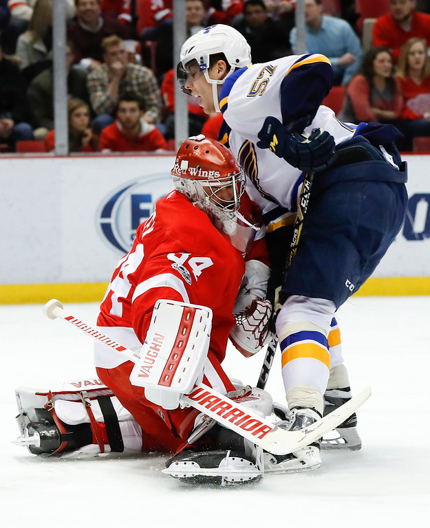 . St. Louis Blues left wing David Perron (57) collides with Detroit Red Wings goalie Petr Mrazek (34) in the first period of an NHL hockey game Wednesday, Feb. 15, 2017, in Detroit. (AP Photo/Paul Sancya)