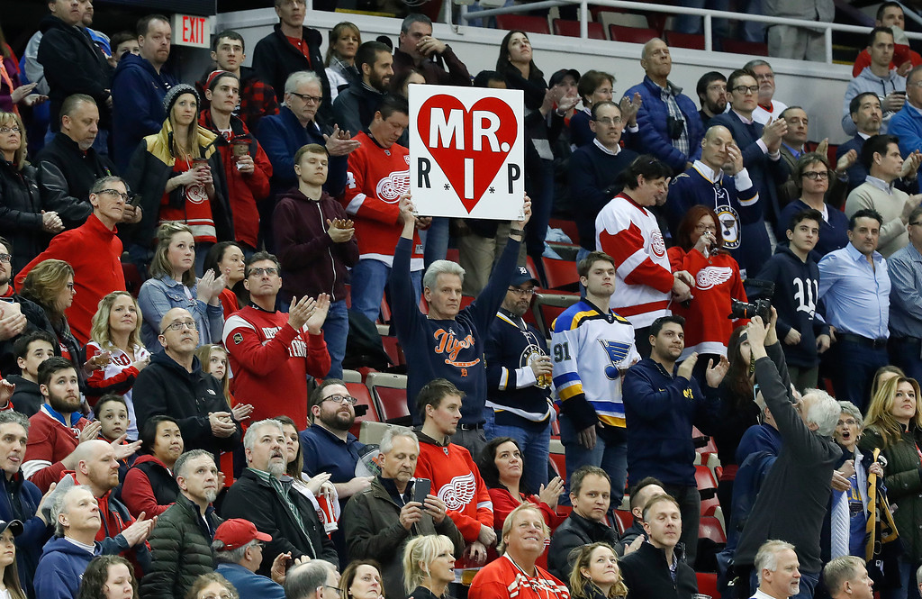 . Hank Stawasz holds a sign in a tribute to Mike Ilitch at Joe Louis Arena before an NHL hockey game between the Detroit Red Wings and St. Louis Blues, Wednesday, Feb. 15, 2017, in Detroit. Billionaire businessman Ilitch, who founded the Little Caesars pizza empire before buying the Detroit Red Wings and Detroit Tigers died Friday. He was 87. (AP Photo/Paul Sancya)