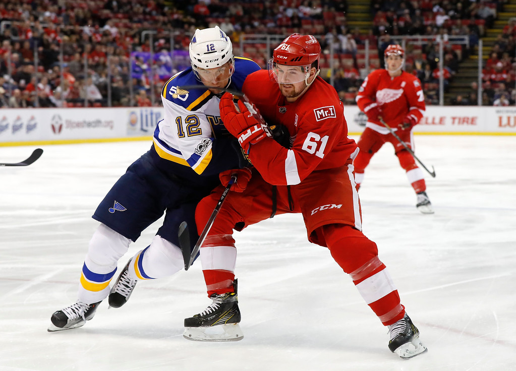 . St. Louis Blues center Jori Lehtera (12) and Detroit Red Wings defenseman Xavier Ouellet (61) battle for position in the first period of an NHL hockey game, Wednesday, Feb. 15, 2017, in Detroit. (AP Photo/Paul Sancya)