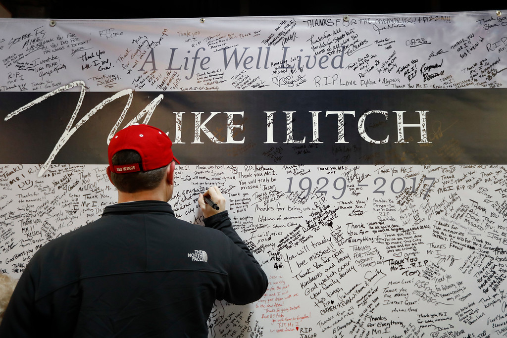 . A well wisher signs a card for Mike Ilitch at Joe Louis Arena before an NHL hockey game between the Detroit Red Wings and St. Louis Blues, Wednesday, Feb. 15, 2017, in Detroit. Billionaire businessman Ilitch, who founded the Little Caesars pizza empire before buying the Detroit Red Wings and Detroit Tigers died Friday. He was 87. (AP Photo/Paul Sancya)