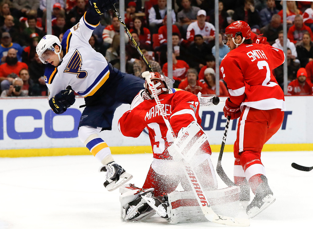 . St. Louis Blues left wing David Perron (57) collides with Detroit Red Wings goalie Petr Mrazek (34) in the first period of an NHL hockey game, Wednesday, Feb. 15, 2017, in Detroit. (AP Photo/Paul Sancya)