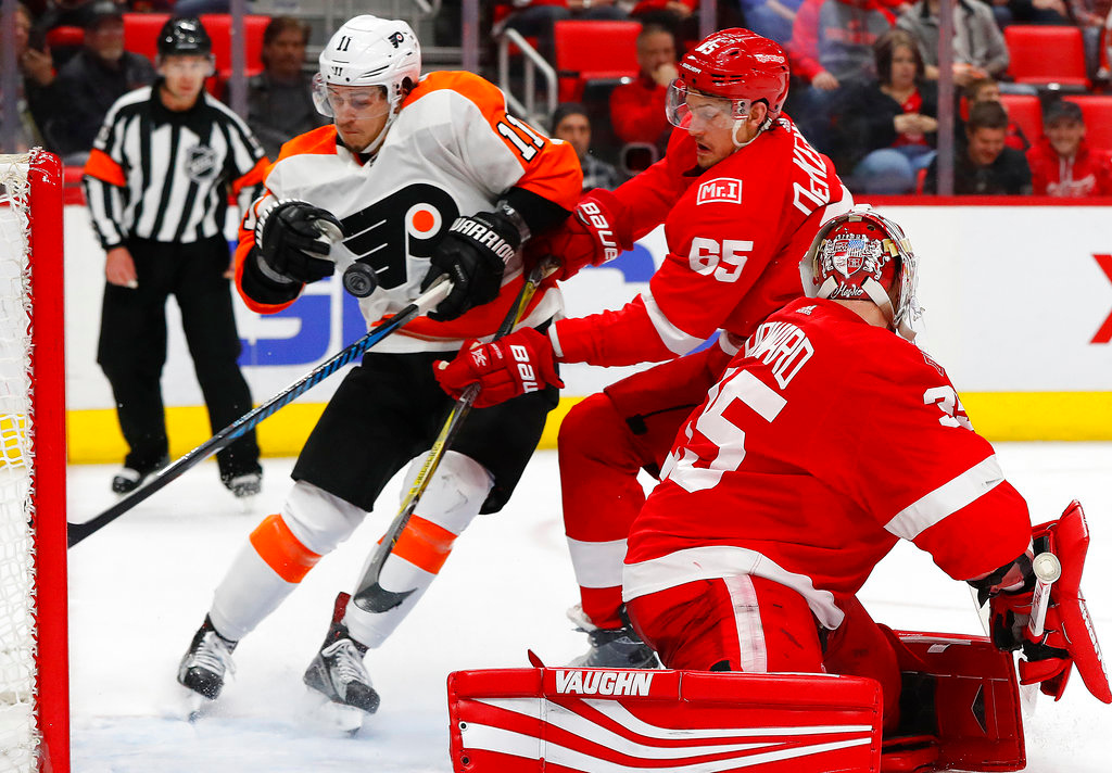 . Philadelphia Flyers center Travis Konecny (11) scores on Detroit Red Wings goaltender Jimmy Howard (35) as Danny DeKeyser (65) defends during the third period of an NHL hockey game Tuesday, March 20, 2018, in Detroit. (AP Photo/Paul Sancya)