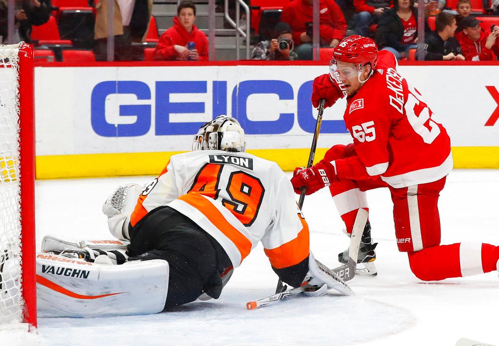 . Philadelphia Flyers goaltender Alex Lyon (49) stops a Detroit Red Wings defenseman Danny DeKeyser (65) shot during overtime in an NHL hockey game Tuesday, March 20, 2018, in Detroit. (AP Photo/Paul Sancya)