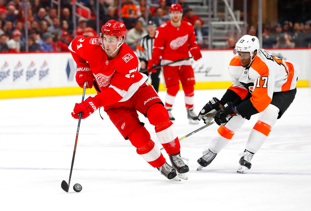 . Detroit Red Wings center Dylan Larkin (71) skates past Philadelphia Flyers right wing Wayne Simmonds (17) in the second period of an NHL hockey game Tuesday, March 20, 2018, in Detroit. (AP Photo/Paul Sancya)