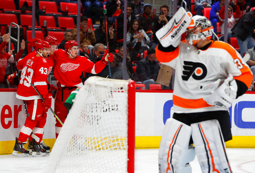. Detroit Red Wings center Dylan Larkin, third from left, celebrates scoring on Philadelphia Flyers goaltender Petr Mrazek, right, in the second period of an NHL hockey game Tuesday, March 20, 2018, in Detroit. (AP Photo/Paul Sancya)