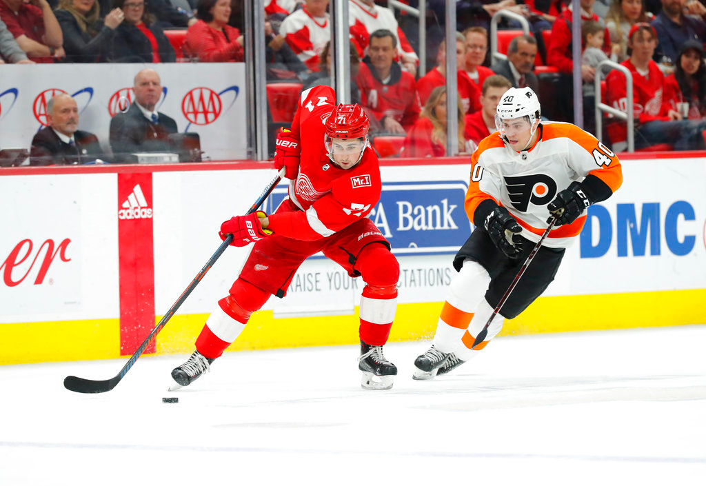 . Detroit Red Wings center Dylan Larkin (71) protects the puck from Philadelphia Flyers center Jordan Weal (40) in the first period of an NHL hockey game Tuesday, March 20, 2018, in Detroit. (AP Photo/Paul Sancya)