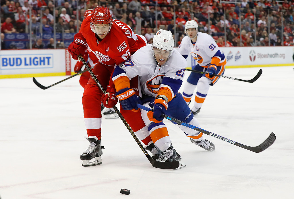 . Detroit Red Wings defenseman Danny DeKeyser (65) and New York Islanders left wing Anders Lee (27) battle for the puck in the third period of an NHL hockey game, Tuesday, Feb. 21, 2017, in Detroit. (AP Photo/Paul Sancya)