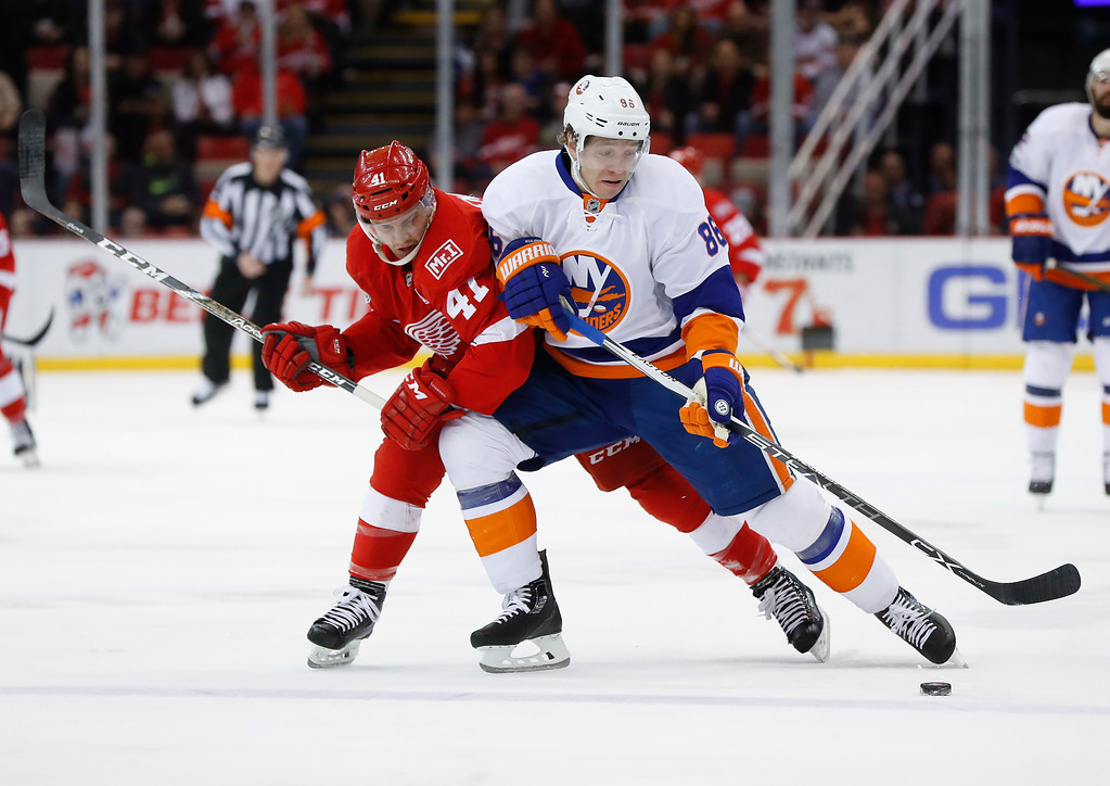 . New York Islanders left wing Nikolay Kulemin (86) protects the puck from Detroit Red Wings center Luke Glendening (41) in the first period of an NHL hockey game, Tuesday, Feb. 21, 2017, in Detroit. (AP Photo/Paul Sancya)