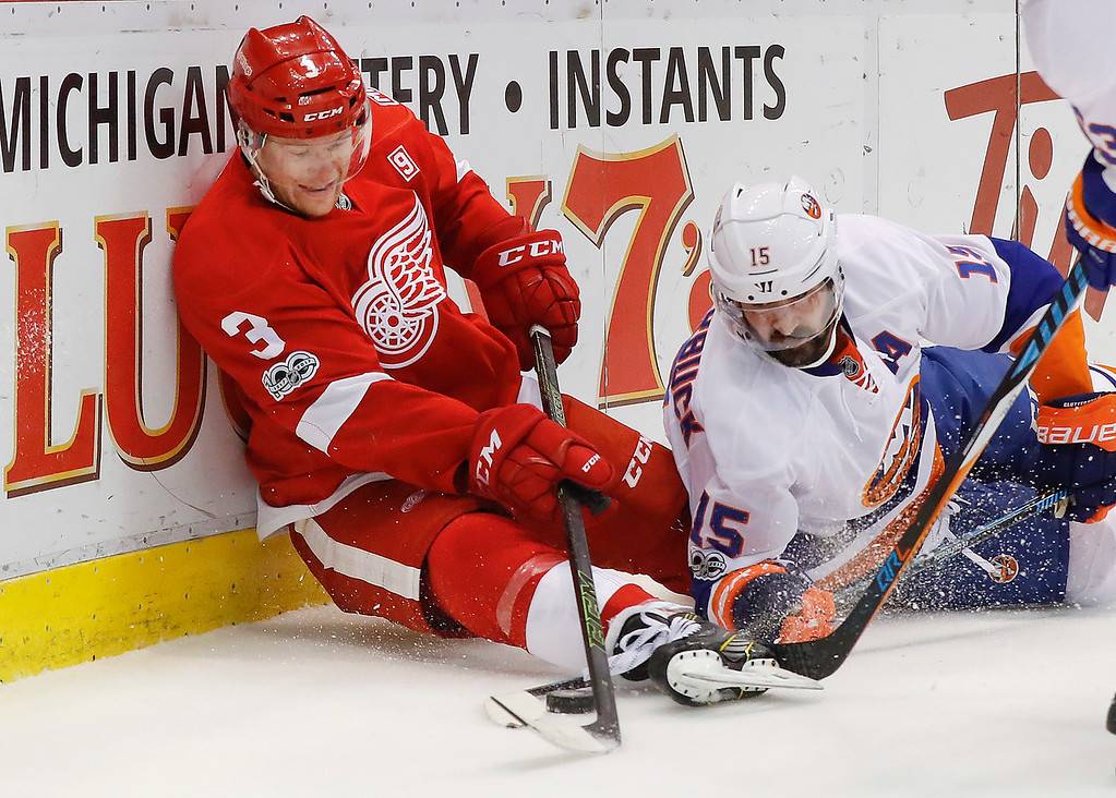 . Detroit Red Wings defenseman Nick Jensen (3) and New York Islanders right wing Cal Clutterbuck (15) battle for the puck in the first period of an NHL hockey game, Tuesday, Feb. 21, 2017, in Detroit. (AP Photo/Paul Sancya)