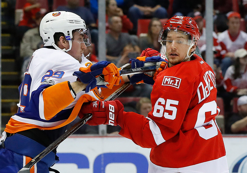 . New York Islanders center Brock Nelson (29) and Detroit Red Wings defenseman Danny DeKeyser (65) battle for position in the first period of an NHL hockey game, Tuesday, Feb. 21, 2017, in Detroit. (AP Photo/Paul Sancya)