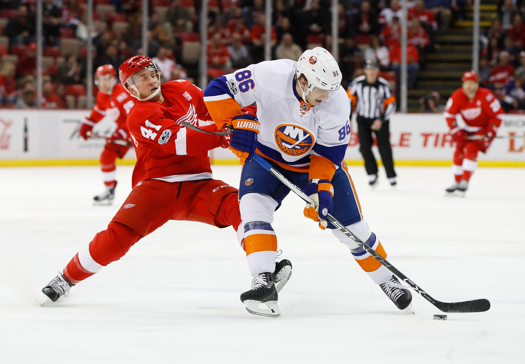 . New York Islanders left wing Nikolay Kulemin (86) protects the puck from Detroit Red Wings center Luke Glendening (41) in the first period of an NHL hockey game Tuesday, Feb. 21, 2017, in Detroit. (AP Photo/Paul Sancya)