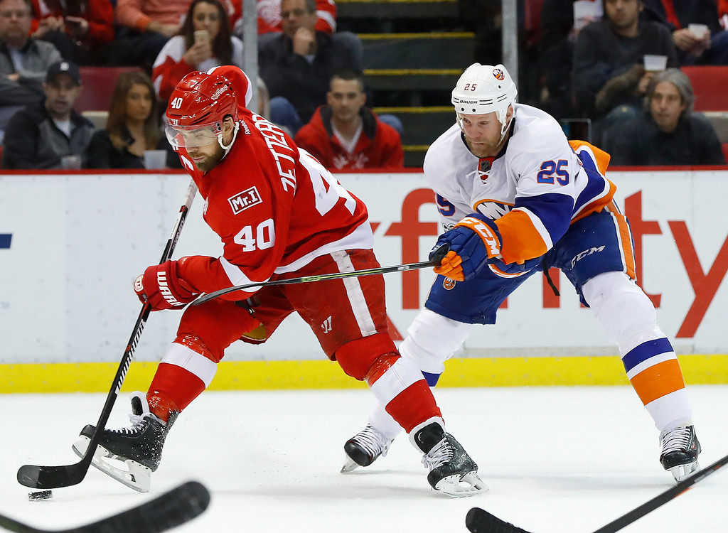 . Detroit Red Wings left wing Henrik Zetterberg (40) skates with the puck as New York Islanders left wing Jason Chimera (25) defends in the second period of an NHL hockey game Tuesday, Feb. 21, 2017, in Detroit. (AP Photo/Paul Sancya)
