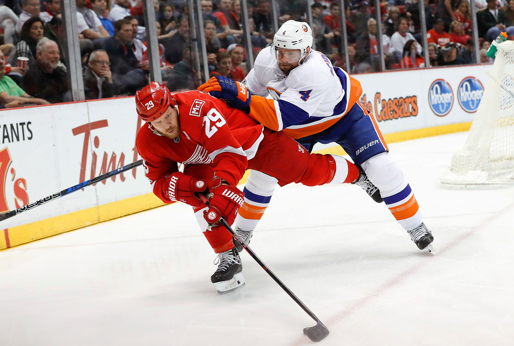 . New York Islanders defenseman Dennis Seidenberg (4) checks Detroit Red Wings center Steve Ott (29) in the second period of an NHL hockey game, Tuesday, Feb. 21, 2017, in Detroit. (AP Photo/Paul Sancya)