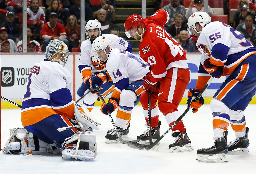 . New York Islanders goalie Thomas Greiss (1) stops a Detroit Red Wings center Darren Helm (43) shot in the second period of an NHL hockey game Tuesday, Feb. 21, 2017, in Detroit. (AP Photo/Paul Sancya)