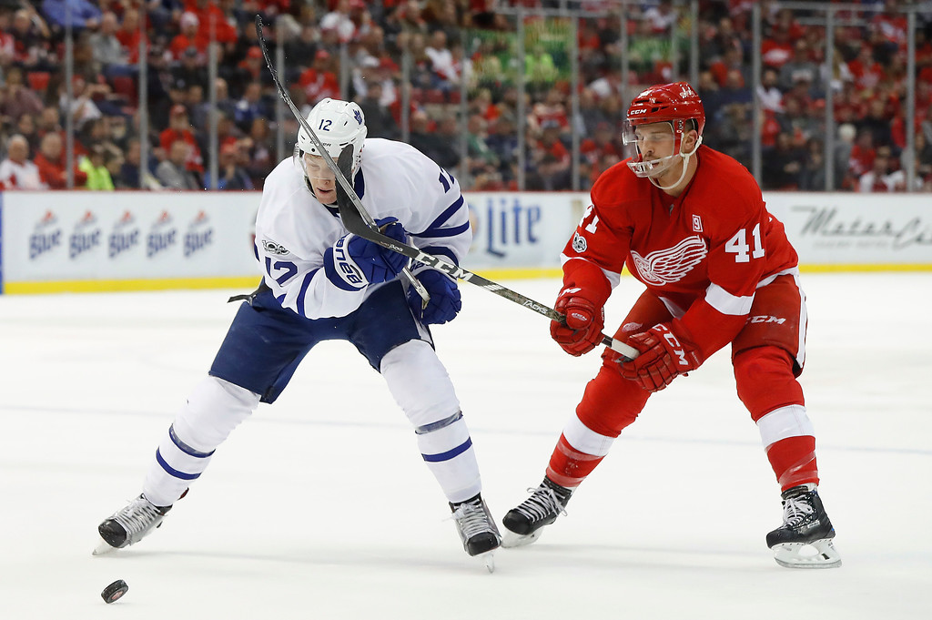. Detroit Red Wings center Luke Glendening (41) lifts the stick of Toronto Maple Leafs right wing Connor Brown (12) in the first period of an NHL hockey game Wednesday, Jan. 25, 2017, in Detroit. (AP Photo/Paul Sancya)