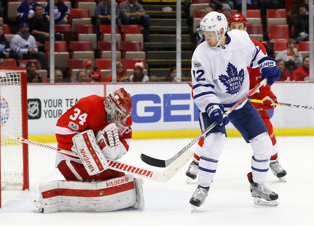 . Detroit Red Wings goalie Petr Mrazek (34) stops a shot as Toronto Maple Leafs right wing Connor Brown (12) waits for a rebound during the third period of an NHL hockey game Wednesday, Jan. 25, 2017, in Detroit. Toronto won 4-0. (AP Photo/Paul Sancya)