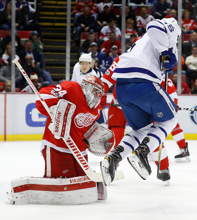 . Toronto Maple Leafs left wing Matt Martin (15) jumps as Detroit Red Wings goalie Petr Mrazek (34) stops a shot in the first period of an NHL hockey game Wednesday, Jan. 25, 2017, in Detroit. (AP Photo/Paul Sancya)