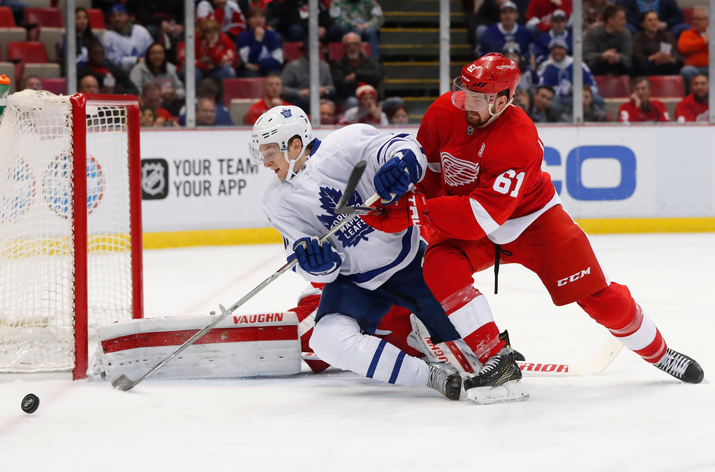 . Detroit Red Wings defenseman Xavier Ouellet (61) knocks Toronto Maple Leafs center Zach Hyman (11) off the puck as he shoots in the first period of an NHL hockey game Wednesday, Jan. 25, 2017, in Detroit. (AP Photo/Paul Sancya)