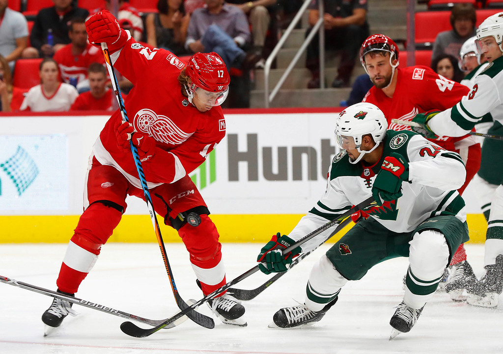 . Detroit Red Wings left wing David Booth (17) and Minnesota Wild defenseman Matt Dumba (24) battle for the puck in the second period of an NHL hockey game Thursday, Oct. 5, 2017, in Detroit. (AP Photo/Paul Sancya)