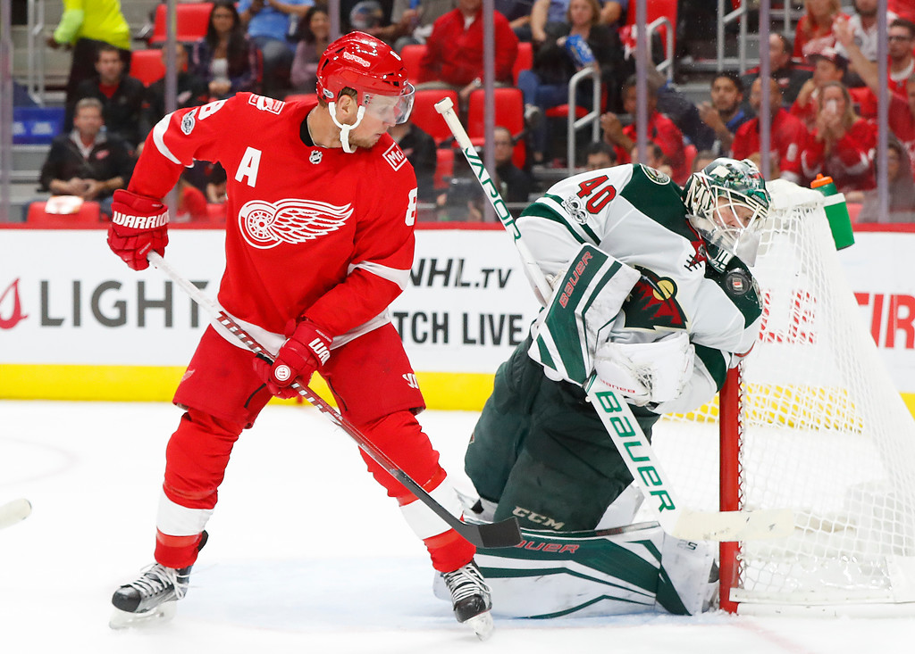 . Minnesota Wild goalie Devan Dubnyk (40) deflects the puck off his mask as Detroit Red Wings left wing Justin Abdelkader (8) looks on in the second period of an NHL hockey game Thursday, Oct. 5, 2017, in Detroit. (AP Photo/Paul Sancya)