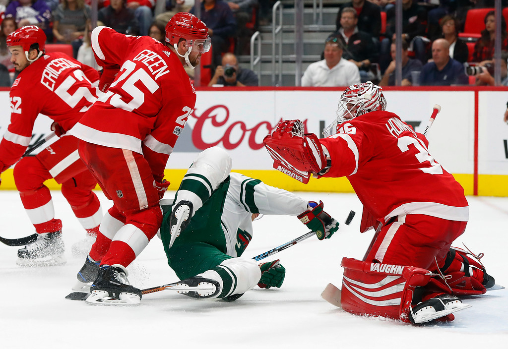 . Minnesota Wild\' Mikael Granlund, of Finland, (64) hits the ice as Detroit Red Wings defenseman Mike Green (25) defends and goalie Jimmy Howard (35) reaches for the puck in the first period of an NHL hockey game Thursday, Oct. 5, 2017, in Detroit. The goal was overturned on video replay. (AP Photo/Paul Sancya)