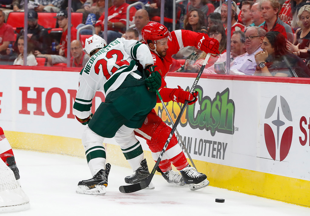 . Minnesota Wild\'s Nino Niederreiter, of Switzerland, (22) checks Detroit Red Wings\' Luke Glendening (41) off the puck in the first period of an NHL hockey game Thursday, Oct. 5, 2017, in Detroit. (AP Photo/Paul Sancya)