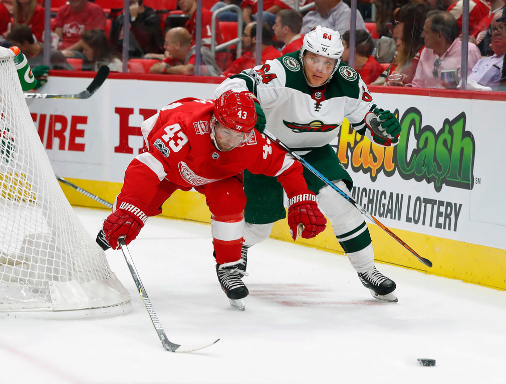 . Detroit Red Wings left wing Darren Helm (43) and Minnesota Wild right wing Mikael Granlund, of Finland, (64) battle for the puck in the first period of an NHL hockey game Thursday, Oct. 5, 2017, in Detroit. (AP Photo/Paul Sancya)