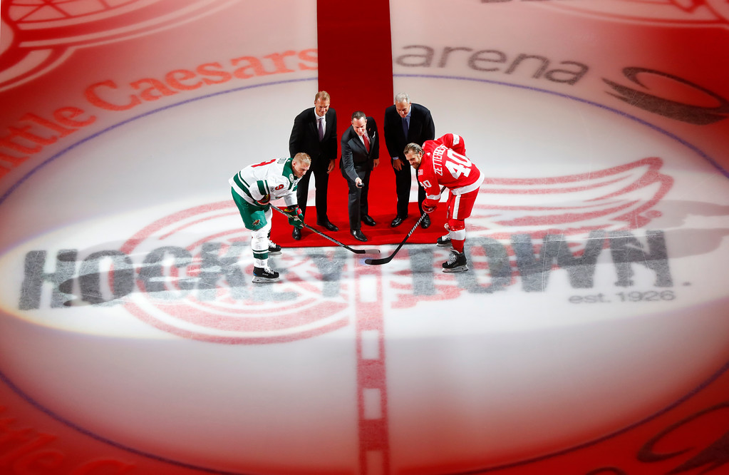 . Christopher Ilitch, president and CEO of Ilitch Holdings, drops a ceremonial puck for Minnesota Wild center Mikko Koivu, of Finland, (9) and Detroit Red Wings center Henrik Zetterberg, of Sweden (40) before an NHL hockey game Thursday, Oct. 5, 2017, in Detroit. (AP Photo/Paul Sancya)