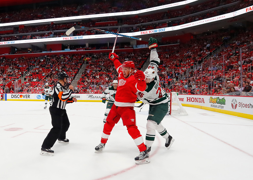 . Detroit Red Wings left wing Justin Abdelkader (8) and Minnesota Wild defenseman Jonas Brodin, of Sweden (25) battle for position in the second period of an NHL hockey game Thursday, Oct. 5, 2017, in Detroit. (AP Photo/Paul Sancya)