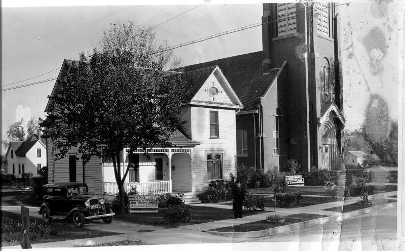 """St Catherines and Parsonage 1920s - St. Catherine's first church was built in 1884, it was then called """"Our Lady of the Cataract"""" (in Latin Lady of the Falls).  The rectory was erected in 1897 and the brick church structure in 1914.  The old wood church still has a presence in RF.  It was cut in two and made into houses.  One is on Broadway--one hundred east, and the other on 2nd.  The latter is the home of Randy Dahmes.  The brick church and rectory came down in 1982 upon completion of the east side of today's church.<br /> That's the history in a nutshell"""