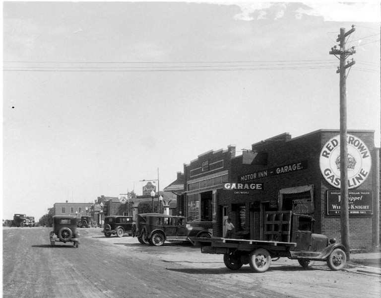"Case 192Xb - You can read the sign, ""CASE"" high up on the front of the building.  It is right beside the Motor Inn Garage.  I believe that the next two photos were taken in the 1920s, and possibly in the early 1920s.  That was about when they installed those cool looking street lights and paved the streets in town.  Actually the next two photos are from the same negative.  I think that I see the building in the left of the photo, which was much later occupied by the Jolly Mill and then the next building, I think was the roof of the Scenic City Co-op building which was built on the southeast corner of Mill and Second, but it is a bit hard to tell for sure. - Roger Breckenridge"
