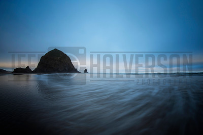 Haystack Rock at daybreak with Pacific Ocean rolling in.