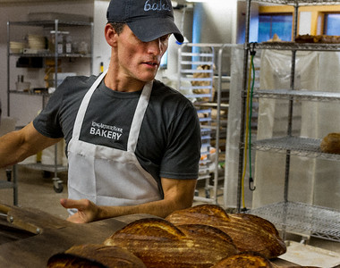 Martin Philip checks on loaves of bread in the oven at the King Arthur Flour Bakery
