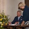 Prince Charles and Camilla signing the visitors book at Salle Church
