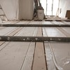 The heating pipes laid into the insulation between the joists on the Miss Owen Gallery
