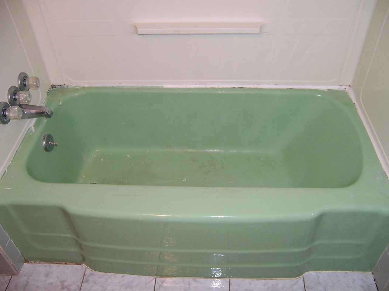 BEFORE - The customer wanted a nuetral color.  Notice the mold on the caulking. This was a health hazzard and made the tub and bathroom seem 'dirty'. In order to beat the mold circle, all the caulking and moisture must be completely removed and replaced. That includes the area under the bottom edge of the surround.