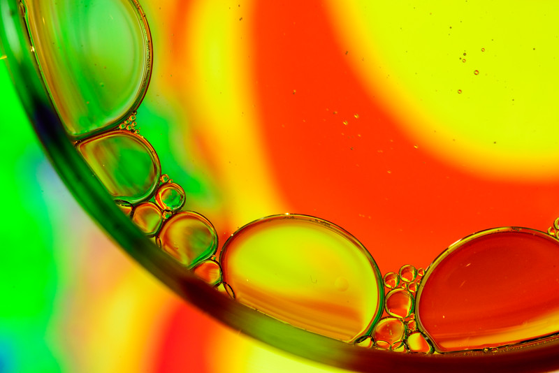Oil and Water in a glass above a colorful backgroud
