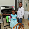 Sarah Nyiramana Bayavuge, 6, and Dusenge Tuyishime, 14, are refugees from the Democratic Republic of Congo who recently settled in Lowell after living in a refugee camp for decades in Uganda with their family. They stand in the kitchen of their new home on Monday. SUN/JOHN LOVE